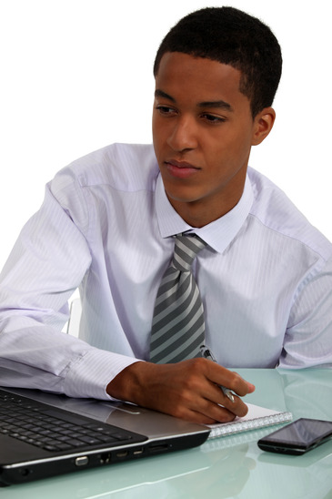 businessman on laptop writing on a piece of paper