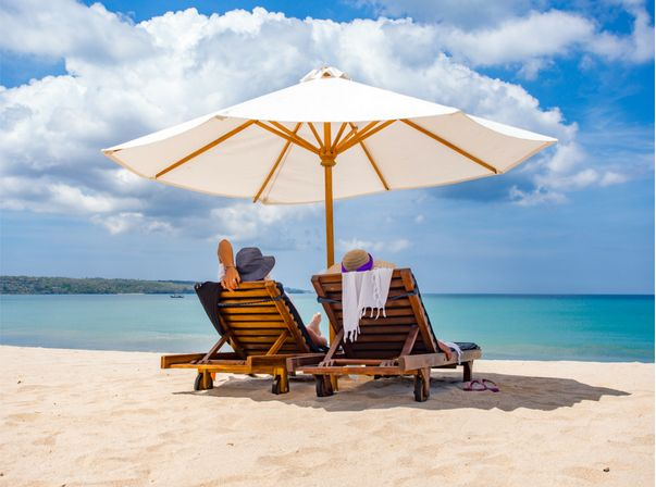 Two people on a sunny beach resting under an umbrella
