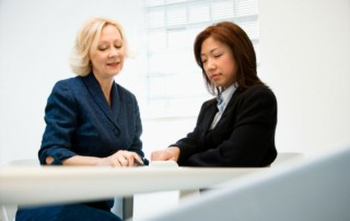 Two businesswomen checking a document and talking