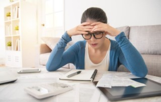 Worried young woman calculating debts