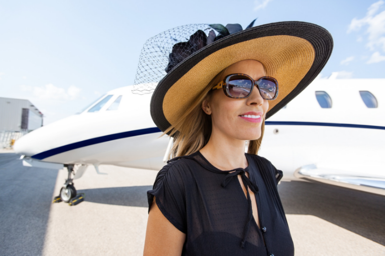 Rich lady in front of a plane