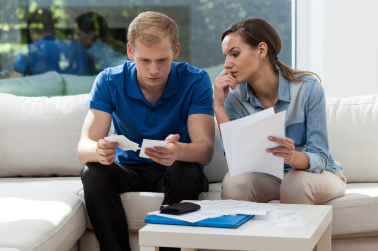 Young couple checking unpaid bills